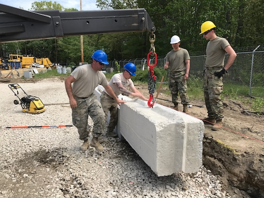Airmen of the 157th Civil Engineer Squadron and Soldiers of Detachment 2, 160th Engineer Company place a block May 21, 2017, at  Pease Air National Guard Base, N.H. The joint team of New Hampshire National Guard members collaborated on four construction projects during a two-week training period. (U.S. Air National Guard Photo By Master Sgt. Thomas Johnson)