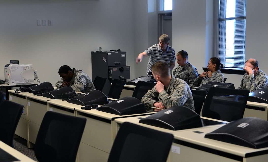 Patrick Geagon, force development McChord testing center test control officer, shows Airmen how to access test material May 25, 2017, at Joint Base Lewis-McChord, Wash. Annually, the testing center administers more than 5,000 tests and can issue up to 250 tests weekly. (U.S. Air Force photo/Senior Airman Jacob Jimenez)