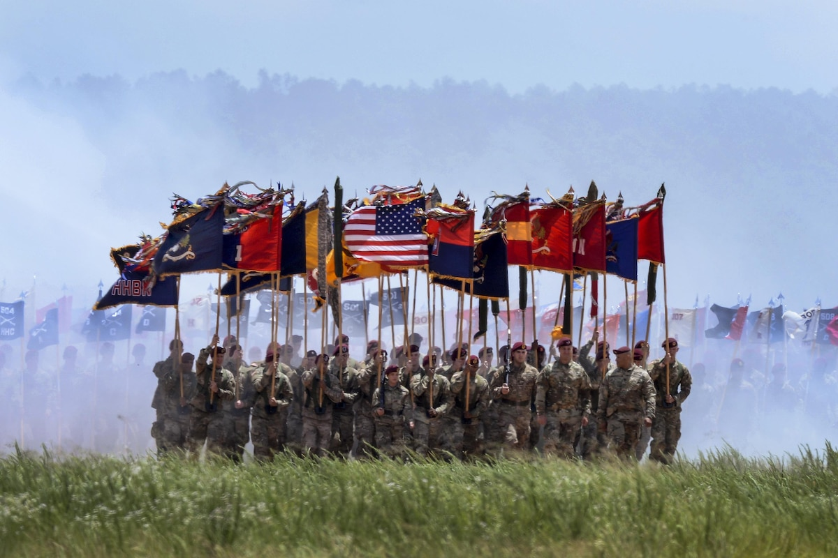 Soldiers carry flags as they march during a review.