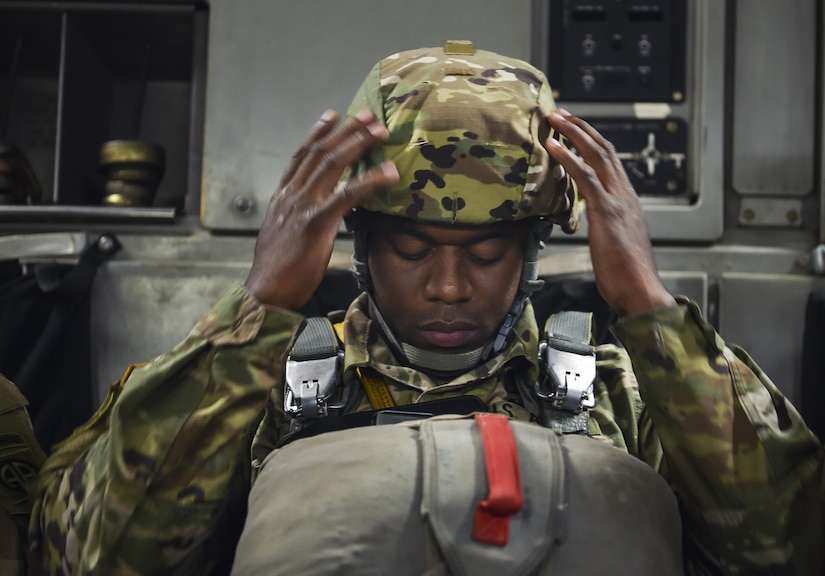"""Army Staff Sgt. Primus Treavor, 82nd Airborne Division maintenance control supervisor, adjusts his helmet in a C-17 Globemaster III from Joint Base Charleston, S.C., May 25, 2017. The 82nd Abn. Div. celebrated their 100th anniversary during """"All American Week"""" with a planned jump from the large formation exercise."""