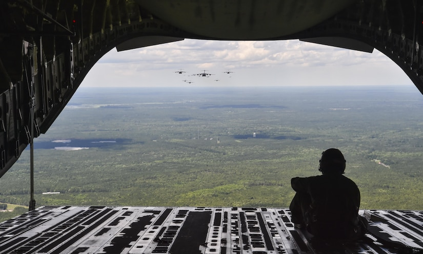 Senior Airman Cory Dye, 14th Airlift Squadron loadmaster, looks out of the cargo door of a C-17 Globemaster III during a large formation exercise, May 25, 2017. The formation contained 18 personnel loaded C-17 Globemaster IIIs and three equipment carrying C-17s from Joint Base Charleston, S.C.