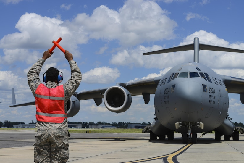 Senior Airman Ezekiel Metz, 315th Aircraft Maintenance Squadron crew chief, marshals in a C-17 Globemaster III from Joint Base Charleston, S.C., supporting a global response force exercise, May 25, 2017. Twenty one C-17s were involved in the integrated large formation exercise supporting the U.S. Army's 82nd Airborne Division's joint forcible entry exercise at Fort Bragg, N.C., as part of All American Week and the 82nd Abn. Div.'s 100th anniversary. (U.S. Air Force photo by Senior Airman Thomas T. Charlton)