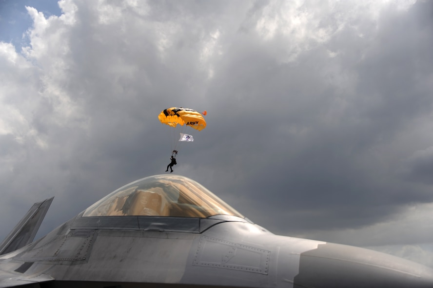 An Army Golden Knights Parachute Team member soars over an Air Force F-22 Raptor during the Memorial Day weekend National Salute to America's Heroes Miami Air and Sea Show at U.S. Coast Guard Air Station Miami in Opa-Locka, Fla., May 26, 2017. Air Force, Army, Navy, Marine Corps, and Coast Guar service members are participating in the air and sea show to demonstrate their capabilities to the public, educate, and increase awareness of each branch's unique mission and role. (U.S. Air Force photo by Senior Airman Erin Trower)
