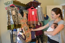 Evan Menendez, with her youngest child, Stevie, in her arms, display some of the designs for girls in the Evan Brooke's Ethical Clothing inventory in her home, May 24, 2017.  The clothing line provides jobs and assistance to those affected by human trafficking. (U.S. Air Force photo by Minnie Jones)