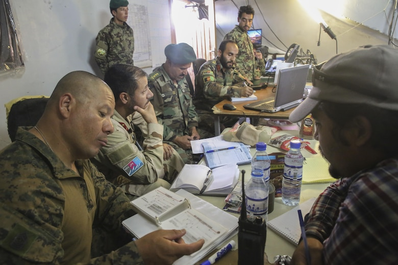 A U.S. Marine advisor with Task Force Southwest and Afghan National Army soldiers with 2nd Brigade, 215th Corps monitor battlefield operations at the Brigade's command operations center in Camp Nolay, Afghanistan, May 23, 2017. Approximately 10 advisors completed an expeditionary advising package May 21-25, helping to facilitate a clearing operation conducted by 3rd Kandak, 2nd Brigade, and worked to improve force sustainment procedures with their Afghan counterparts. (U.S. Marine Corps photo by Sgt. Lucas Hopkins)