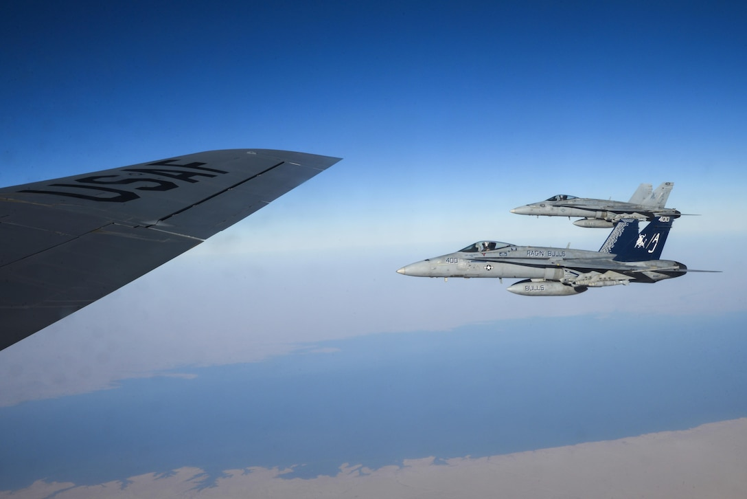 Two U.S. Navy F/A-18Cs from the Strike Fighter Squadron VFA-37 Ragin' Bulls fly in formation alongside a U.S. Air Force KC-135 Stratotanker during a combat refueling mission over Southwest Asia May 21, 2017.  KC-135 Stratotankers, from the 340th Expeditionary Air Refueling Squadron at Al Udeid Air Base, Qatar, maintain a 24/7 presence in the Area Of Responsibility, supporting U.S. and Coalition forces in the air and on the ground, contributing to Operation Inherent Resolve and the fight against ISIS. (U.S. Air National Guard photo by Master Sgt. Andrew J. Moseley/Released)