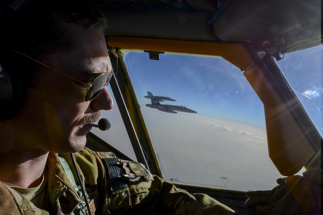 U.S. Air Force Capt. Timothy Black, aircraft commander, pilots a KC-135 Stratotanker on a combat refueling mission over Southwest Asia while two U.S. Navy F/A-18Cs from the VFA-37 Ragin' Bulls fly in formation alongside the aircraft May 21, 2017. Assigned to the 340th Expeditionary Air Refueling Squadron, out of Al Udeid Air Base, Qatar, the tanker from the 186th Air Refueling Wing, Mississippi Air National Guard was fitted with a drogue attached to the boom, for specialized receiver equipment on Navy and coalition aircraft. The 340 EARS maintains a 24/7 presence in the AOR, supporting Operation Inherent Resolve and the fight against ISIS. (U.S. Air National Guard photo by Master Sgt. Andrew J. Moseley/Released)
