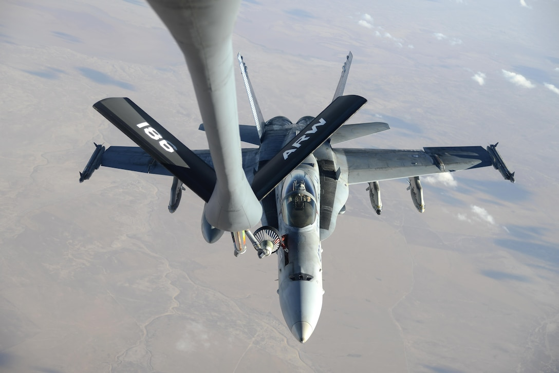 A U.S. Navy F/A-18C from the Strike Fighter Squadron VFA-37 Ragin' Bulls receives fuel in flight from a U.S. Air Force KC-135 Stratotanker over Southwest Asia May 21, 2017. Assigned to the 340th Expeditionary Air Refueling Squadron, out of Al Udeid Air Base, Qatar, the tanker from the 186th Air Refueling Wing, Mississippi Air National Guard was fitted with a drogue attached to the boom, for specialized receiver equipment on Navy and coalition aircraft. The 340th EARS maintains a 24/7 presence in the AOR, extending the missions of aircraft supporting Operation Inherent Resolve and the fight against ISIS. (U.S. Air National Guard photo by Master Sgt. Andrew J. Moseley/Released)