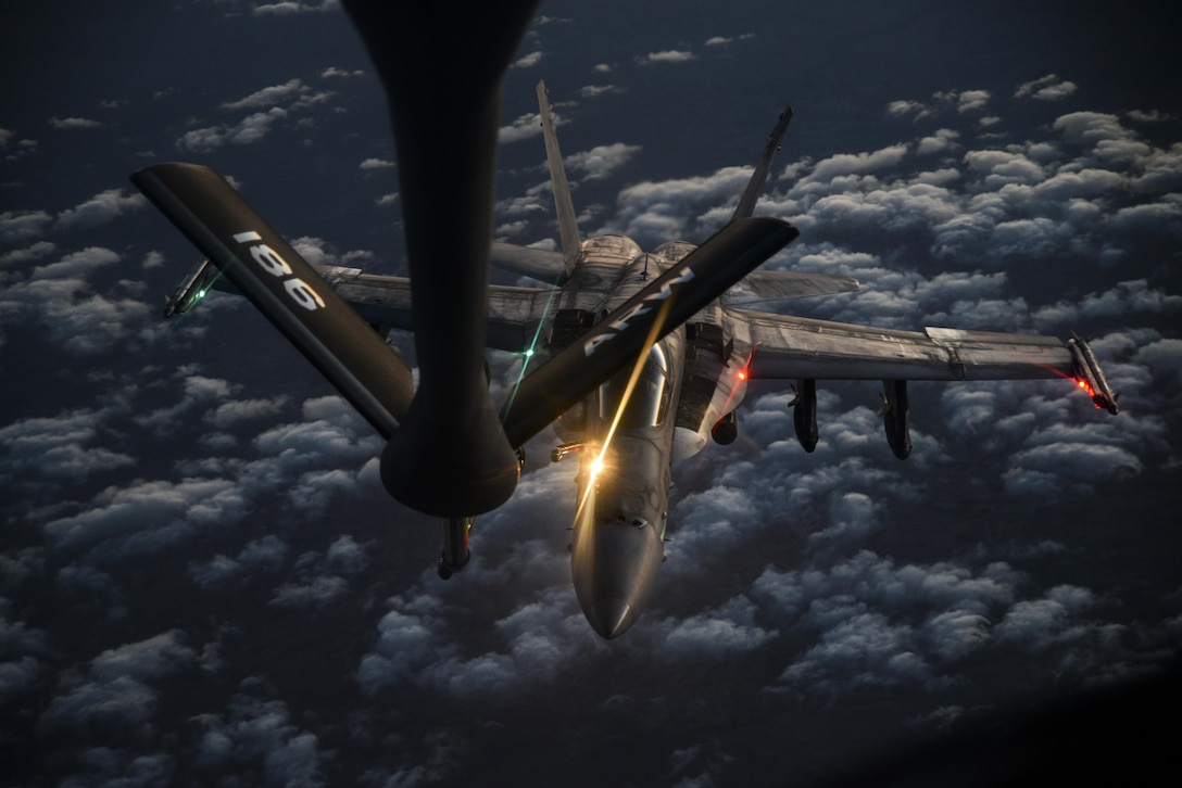 A U.S. Navy F/A-18C from the VFA-37 Ragin' Bulls prepares to receive fuel from a U.S. Air Force KC-135 Stratotanker over Southwest Asia May 21, 2017. Assigned to the 340th Expeditionary Air Refueling Squadron, Al Udeid Air Base, Qatar, the tanker from the 186th Air Refueling Wing, Mississippi Air National Guard is fitted with a drogue attached to the boom, for specialized receiver equipment on Navy and coalition aircraft. The 340 EARS tankers maintain a 24/7 presence in the Area Of Responsibility, supporting U.S. and coalition aircraft participating in Operation Inherent Resolve and the fight against ISIS. (U.S. Air National Guard photo by Master Sgt. Andrew J. Moseley/Released)