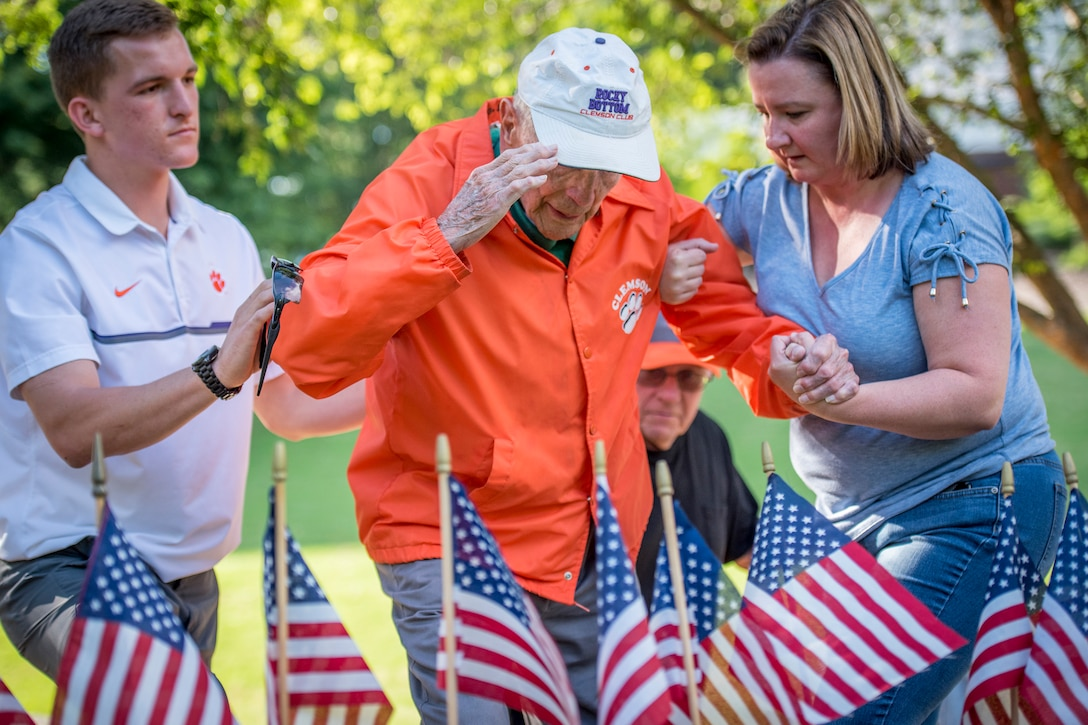 Retired Army Col. Ben Skardon, 99, a survivor of the Bataan Death March, salutes Henry Leitner's headstone in Clemson University's Scroll of Honor