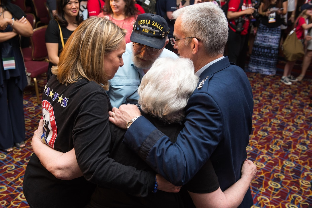 Ms. Bonnie Carroll, TAPS President and Founder, left, and Air Force Gen. Paul J. Selva, vice chairman of the Joint Chiefs of Staff, embrace the mother and father of U.S. Navy Electronics Technician 1st Class Ronald Hemenway