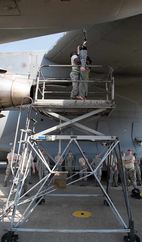 U.S. Air Force Staff Sgt. Henry Thomas III, crew chief assigned to the 728th Air Mobility Squadron, demonstrates how to unhook a training dummy from the wing of a C-17 Globemaster III during fall and rescue training May 25, 2017, at Incirlik Air Base, Turkey. SSgt Thomas also demonstrate the step-by-step process in the fall and rescue procedures. (U.S. Air Force photo by Senior Airman Jasmonet D. Jackson)