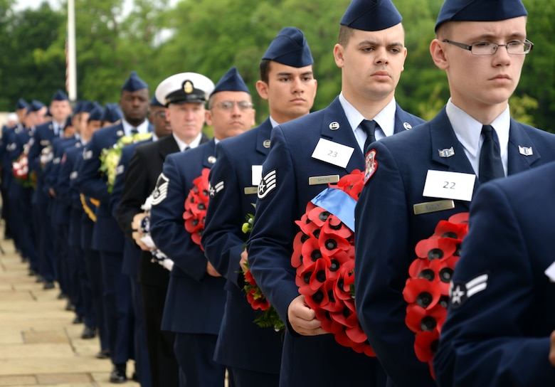 Dozens of Airmen and other U.S. Military Service members carry wreaths donated from several organizations to lay during the Madingley Memorial Day Ceremony May 29, 2017, at Madingley Memorial Cemetery in Cambridge, England. This year volunteers' collected more than 4,000 portraits of veterans to lay at corresponding headstones within the cemetery. (U.S. Air Force photo by Senior Airman Christine Groening)