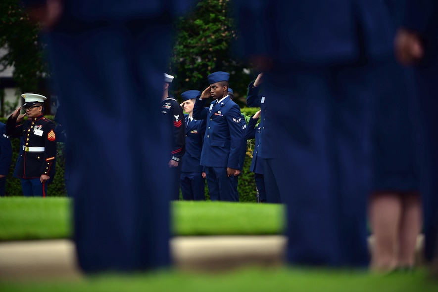 U.S. Service members salute the U.S. flag during the Madingley Memorial Day ceremony May 29, 2017, at Madingley Memorial Cemetery in Cambridge, England. The cemetery is the final resting place for thousands of American veterans. (U.S. Air Force photo by Senior Airman Christine Groening)