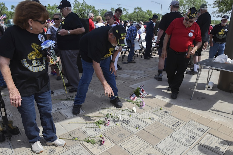 Tom Bright, Vietnam Veterans of America Chapter 457 president, lays a flower on a memorial stone at the San Angelo Regional Airport, Texas, May 29, 2017. The flowers were part of a ceremony to honor the fallen veterans of the Vietnam and other conflicts. (U.S. Air Force photo by Airman 1st Class Chase Sousa/Released)