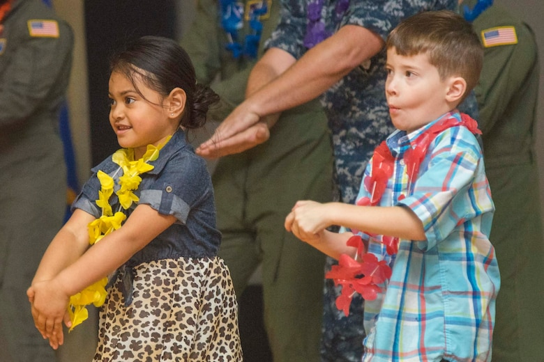 Amytheus Vaa, left, and Braeden O'Donnell, right, Asian American and Pacific Islander Heritage Month Culture Show attendees, participate in a hula dance during the show at Joint Base Andrews, Md., May 24, 2017. The event began with guest speaker, Amata Coleman Radewagen, U.S. congresswoman, followed by AAPI food and performances. (U.S. Air Force photo by Airman 1st Class Valentina Lopez)