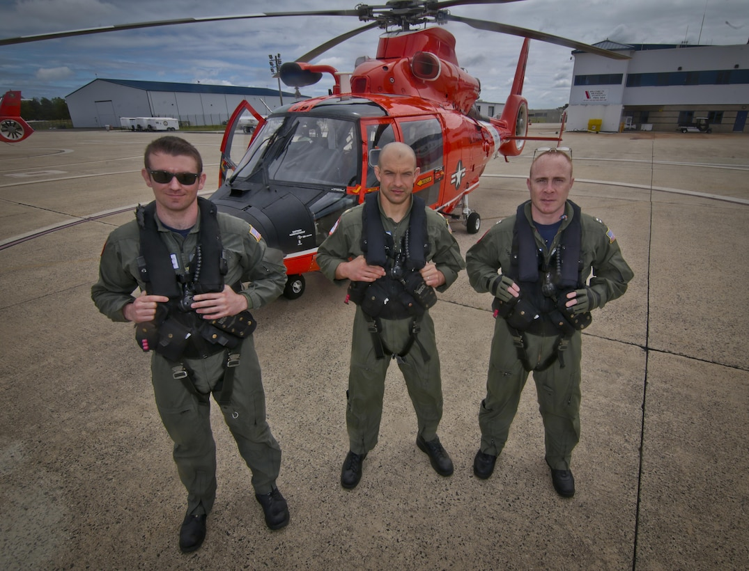 A U.S. Coast Guard HH-65C Dolphin helicopter crew from Coast Guard Air Station Atlantic City stand for a portrait before a mission during a three-day Aeropsace Control Alert CrossTell live-fly training exercise at Atlantic City International Airport, N.J., May 24, 2017. Representatives from the Air National Guard fighter wings, Civil Air Patrol, and U.S. Coast Guard rotary-wing air intercept units will conduct daily sorties from May 23-25 to hone their skills with tactical-level air-intercept procedures. (U.S. Air National Guard photo by Master Sgt. Matt Hecht/Released)