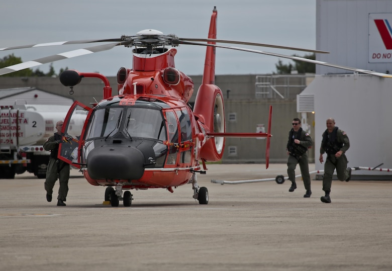 A U.S. Coast Guard HH-65C Dolphin helicopter crew from Coast Guard Air Station Atlantic City rushes to their aircraft after an alert during a three-day Aeropsace Control Alert CrossTell live-fly training exercise at Atlantic City International Airport, N.J., May 24, 2017. Representatives from the Air National Guard fighter wings, Civil Air Patrol, and U.S. Coast Guard rotary-wing air intercept units will conduct daily sorties from May 23-25 to hone their skills with tactical-level air-intercept procedures. (U.S. Air National Guard photo by Master Sgt. Matt Hecht/Released)