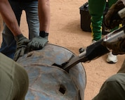A combination spreader tool rips through a metal barrel in Agadez, Niger, May 16, 2017. The combination spreader tool is a hydraulic rescue tool, commonly referred to as the Jaws of Life, firefighters use to extricate a person trapped in an emergency situation. (U.S. Air Force photo by Senior Airman Jimmie D. Pike)