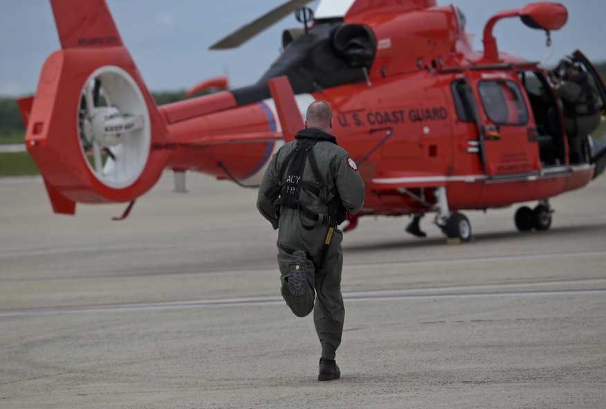 A U.S. Coast Guard HH-65C Dolphin crew member from Coast Guard Air Station Atlantic City runs to his helicopter after an alert during a three-day Aeropsace Control Alert CrossTell live-fly training exercise at Atlantic City International Airport, N.J., May 24, 2017. Representatives from the Air National Guard fighter wings, Civil Air Patrol, and U.S. Coast Guard rotary-wing air intercept units will conduct daily sorties from May 23-25 to hone their skills with tactical-level air-intercept procedures. (U.S. Air National Guard photo by Master Sgt. Matt Hecht/Released)