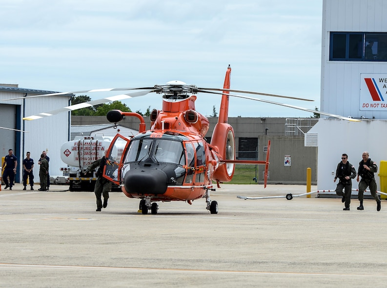 U.S. Coast Guard HH-65C Dolphin crew members from a U.S. Coast Guard Rotary Wing Air Intercept Squadron scramble to their helicopter for an intercept during a CrossTell training exercise at the Atlantic City International Airport, N.J., May 24, 2017. Air National units from New Jersey, South Carolina and Washington D.C. participated in training and familiarization exercises with the U.S. Coast Guard and Civil Air Patrol during the three-day CrossTell to increase awareness of the Aerospace Control Alert mission. (U.S. Air National Guard photo by Airman 1st Class Cristina J. Allen/Released)