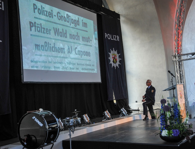 Police Inspector Jürgen Schmitt, Rhineland-Palatinate (RLP) Polizei, looks at a headline about the Polizei's work during the RLP Polizei's 70th year anniversary celebration in Koblenz, Germany, May 20, 2017. Forming alongside RLP, the RLP Polizei initially combated black markets and gang activity after World War II. Now, they are more partners of politics, economics, most importantly the people. (U.S. Air Force photo by Staff Sgt. Timothy Moore)