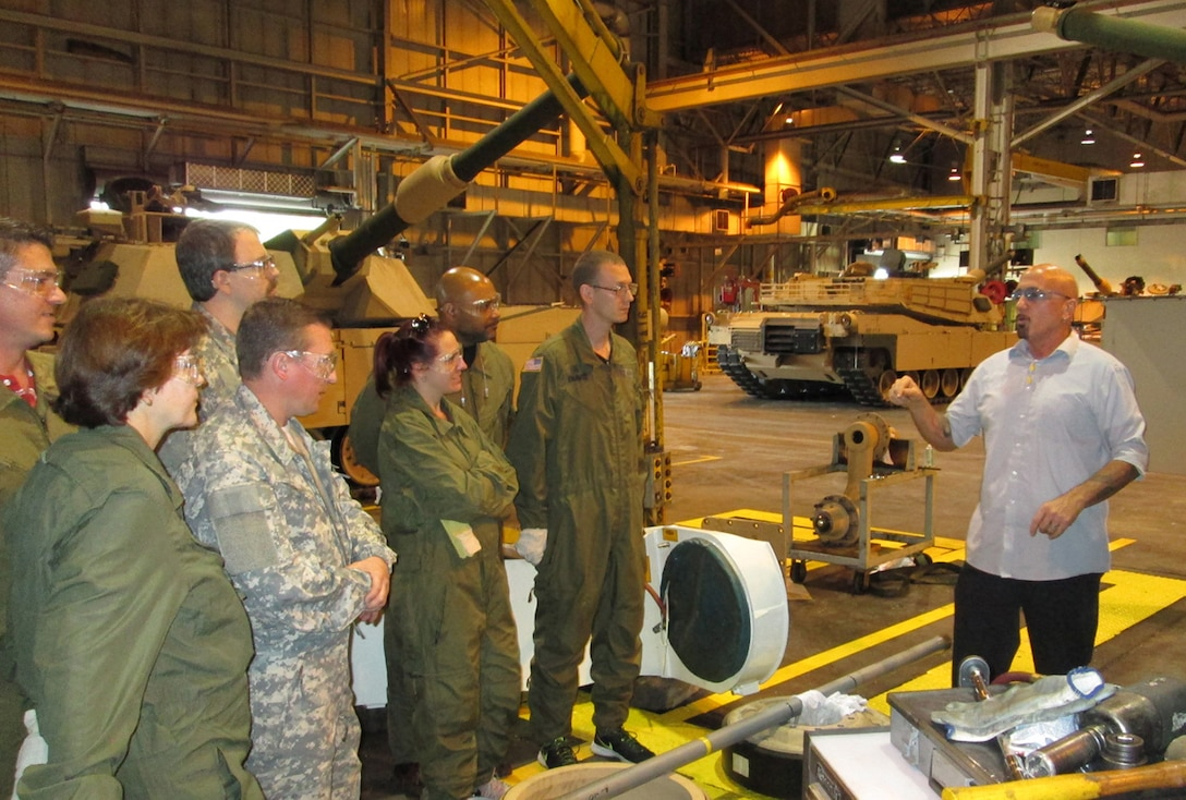 A group of DLA Land and Maritime associates listen to David Hobbs (right), a quality assurance specialist at the Joint Systems Manufacturing Center in Lima, Ohio as he explains the production process of an Abrams Main Battle Tank. The group toured the facility May 16-17 to learn about the production of combat vehicles.