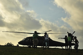 Local children run out to greet a UH-60 Blackhawk helicopter arriving for the medical readiness and training exercise held in Dangriga, Belize, May 22, 2017. The MEDRETE is one of three, carried out as part of Beyond the Horizon 2017, a U.S. Army South partnership exercise with the Government of Belize that consists of five construction projects and three health care events in communities across Belize. (US Army photo by Spc. Nathaniel Free)