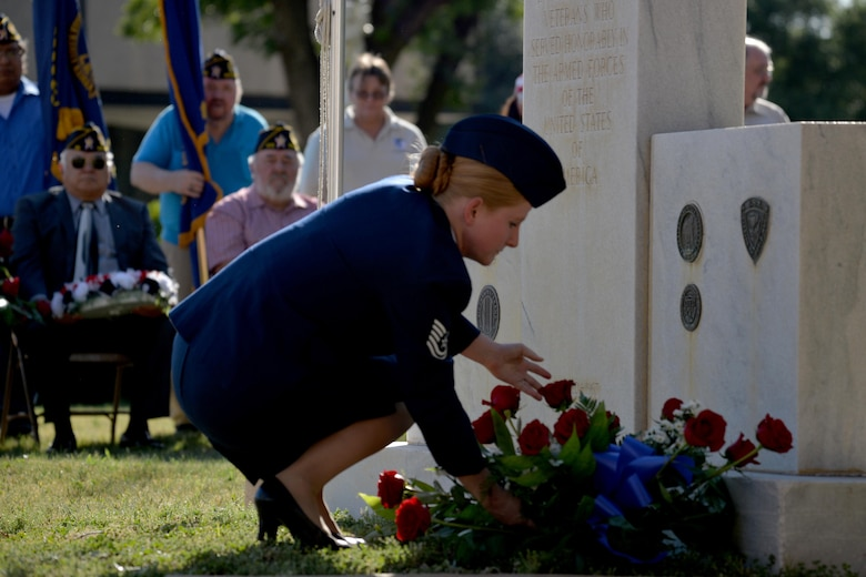 """U.S. Air Force Tech. Sergeant Jessi Baugh, 17 Medical Support Squadron command support staff NCO in charge, places a wreath upon the veteran memorial during the Memorial Day Ceremony at the Tom Green County Courthouse in San Angelo, Texas, May 29, 2017. At the end of the ceremony, members of local veterans' organizations also placed wreaths on the veteran memorial near the courthouse and four retired service members from the All Veterans Council lowered the flag during """"Taps."""" (U.S. Air Force photo by Airman 1st Class Randall Moose/Released)"""
