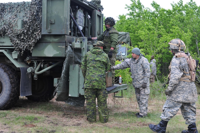 Soldiers from the Canadian Army's 2 Field Ambulance service group fill a fuel can for Spc. Omar Rosario, a heavy wheeled vehicle operator from Avon Park, Florida, during Maple Resolve 17 at Camp Wainwright, Alberta, Canada, on May 24, 2017.  Rosario's unit, the 993rd Transportation Company, provided logistical support during the joint training exercise designed to sharpen individual skill sets and enhance unit readiness. (U.S. Army photo by Sgt. Sarah Zaler)