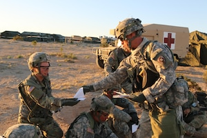 Army Chaplain (Capt.) Steven De Haan, with the Iowa Army National Guard's 1034th Combat Sustainment Support Battalion, hands out a sheet of prayers at Fort Irwin, Calif., April 30, 2017. The unit is at the National Training Center for a three-week rotation. Iowa Army National Guard photo by Spc. Tawny Schmit