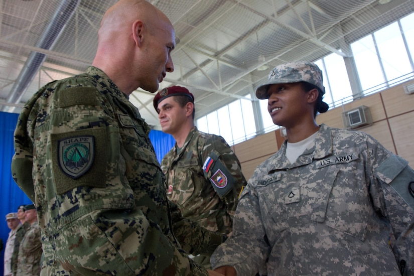 Croatian Command Sgt. Maj. Davor Petek, the command senior enlisted leader for allied command operations at NATO's Supreme Headquarters Allied Powers Europe, greets U.S. Army Pfc. Angel Anderson, at KFOR headquarters at Camp Film City in Pristina, Kosovo, Sept. 4, 2015. Army photo by Sgt. Erick Yates