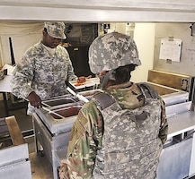 Pvt. Keon Christie, culinary specialist, 2nd General Support Aviation Battalion, 1st Aviation Regiment, 1st Combat Aviation Brigade, 1st Infantry Division, serves food during an inspection April 27. The inspection was part of the Philip A. Connelly Program.