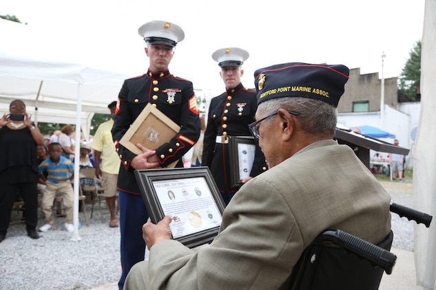 "Archibald Mosley reads a Congressional Gold Medal memento for Montford Point Marines, May 27, at the Colp Area Veterans Celebration, Dedication and Remembrance Ceremony, in Colp, Illinois. Nearly 20,000 African-Americans joined the Marine Corps in 1942, after President Franklin D. Roosevelt issued a ""presidential directive giving African Americans an opportunity to be recruited in the Marine Corps,"" according to the Montford Point Marines Association website. They didn't receive recruit training at San Diego or Parris Island, however, but Camp Montford Point, N.C., a segregated training site for African American Marine recruits. For the next seven years, the camp remained opened until it became desegregated. The four Marines are Sol Griffin, Jr.; James L. Kirby, Early Taylor, Jr. and Archibald Mosley. These Marines, among many other Montford Point Marines across the country, were awarded the Congressional Gold Medal, the highest award that can be given to a civilian by Congress, in 2012. Mosley is one of four Montford Point Marines from Colp. (U.S. Marine Corps photo by Gunnery Sgt. Bryan A. Peterson)"