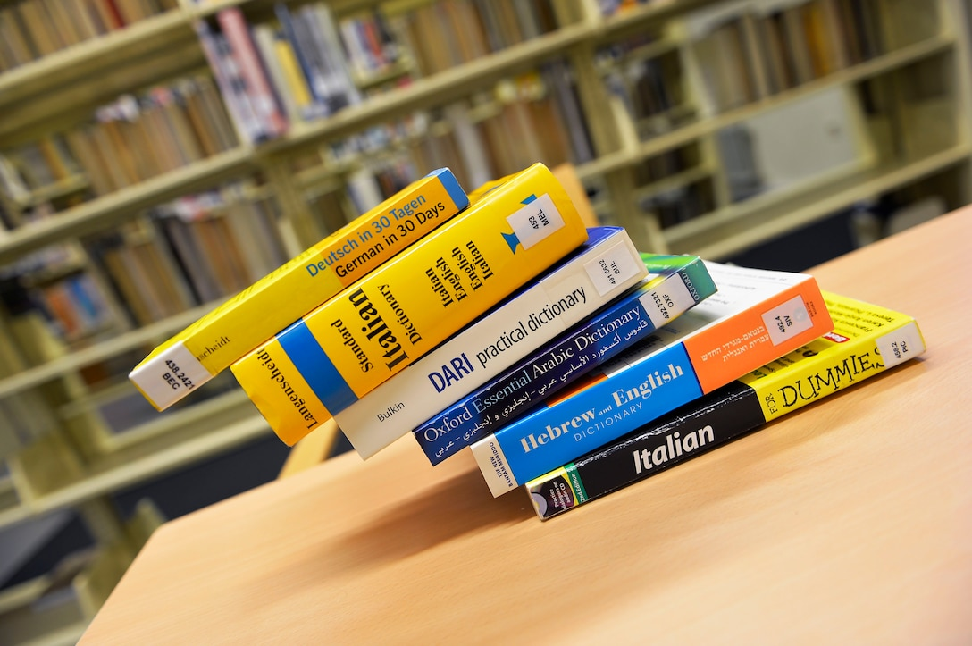 Books about learning foreign languages create the illusion of falling off a table in a library at Ramstein Air base, Germany, May 18, 2017. The Language Enabled Airman Program aims to develop a general purpose force comprised of multi-lingual Airmen from all Air Force specialties. (U.S. Air Force photo by Airman 1st Class Joshua Magbanua)