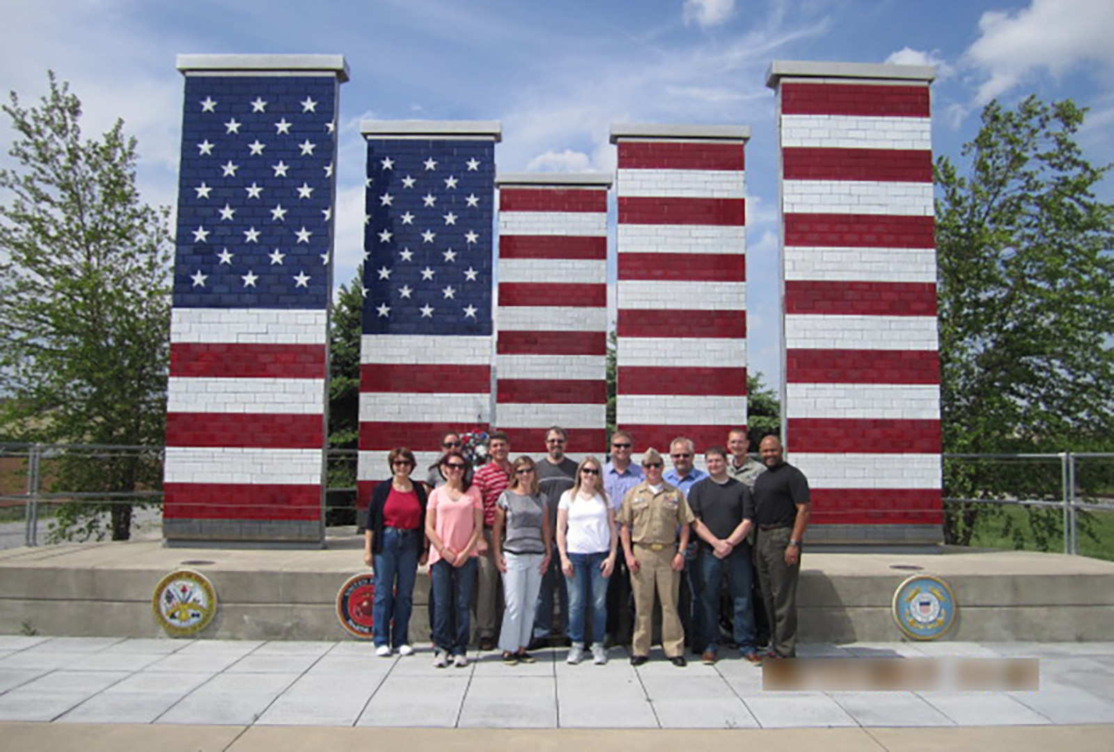 A Department of Defense tour group stands in front of the Veterans Freedom Flag Monument at the Joint Systems Manufacturing Center in Lima, Ohio May 17. The group learned about the production of combat fighting vehicles during a factory tour at the facility.