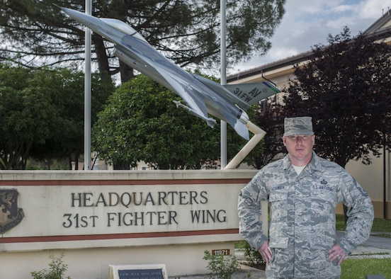 Chief Master Sgt. Michael Alexander stands in front of the 31st Fighter Wing static display on May 26, 2017 at Aviano Air Base, Italy. His portrait is for his commentary on the history of fighter pilots. (U.S. Air Force photo by Senior Airman Cory Bush)