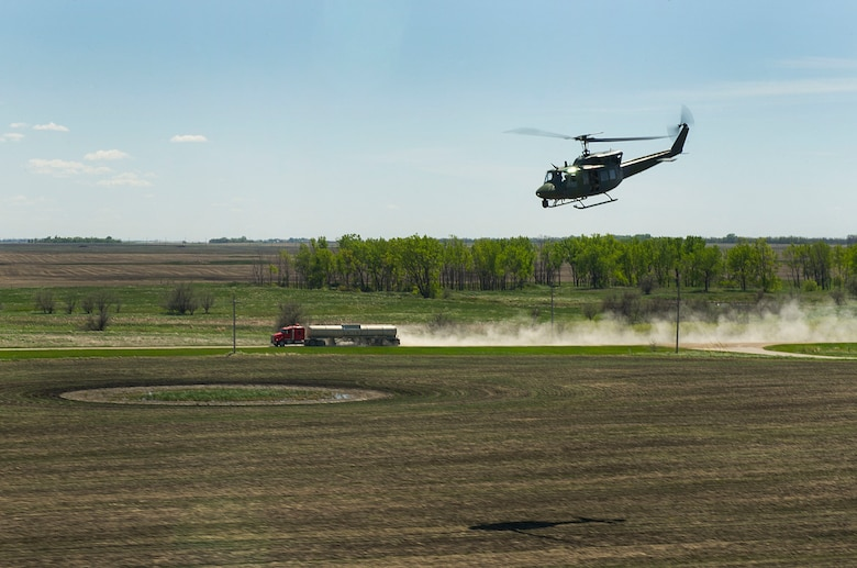 A UH-1N Iroquois huey from the 54th Helicopter Squadron flies alongside a semi-truck during a training sortie in the missile complex, N.D., May 23, 2017. The training sorties prepare aircrews for quick security response in the complex. (U.S. Air Force photo/Senior Airman Apryl Hall)