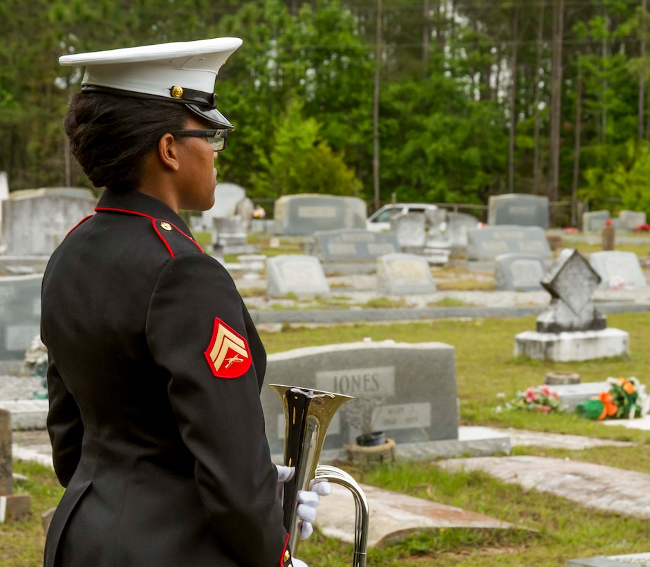 """A Marine with Marine Corps Logistics Base Albany funeral detail waits to play taps at the funeral of Marine Pfc. James O. Whitehurst at Cowarts Baptist Church Cemetery in Cowarts, Alabama, April 12, 2017. Originally composed to signal """"lights out,"""" the tune became a traditional way to honor service members. Whitehurst was killed in action at the battle of Tarawa during World War II, Nov. 23, 1943. (Marine Corps photo by Cpl. Krista James/Released)"""