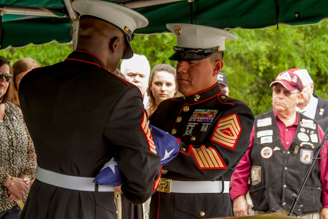 Marines with Marine Corps Logistics Base Albany funeral detail fold the flag that was laid upon the casket of Marine Pfc. James O. Whitehurst before presenting it to his family at Cowarts Baptist Church Cemetery in Cowarts, Alabama, April 12, 2017. Each fold represents something different and at the end only the stars are left showing on the top. Whitehurst was killed in action at the battle of Tarawa during World War II, Nov. 23, 1943. (Marine Corps photo by Cpl. Krista James/Released)