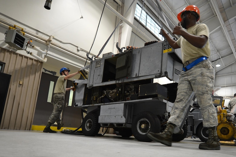 U.S. Airmen assigned to the 20th Equipment Maintenance Squadron aerospace ground equipment (AGE) flight use a lift to remove the top of an A/M32A-60 generator at Shaw Air Force Base, S.C., May 24, 2017. Airmen assigned to the AGE flight utilize an array of tools and machinery to perform repairs on any and all aircraft maintenance equipment that enters the work center. (U.S. Air Force photo by Airman 1st Class Christopher Maldonado)
