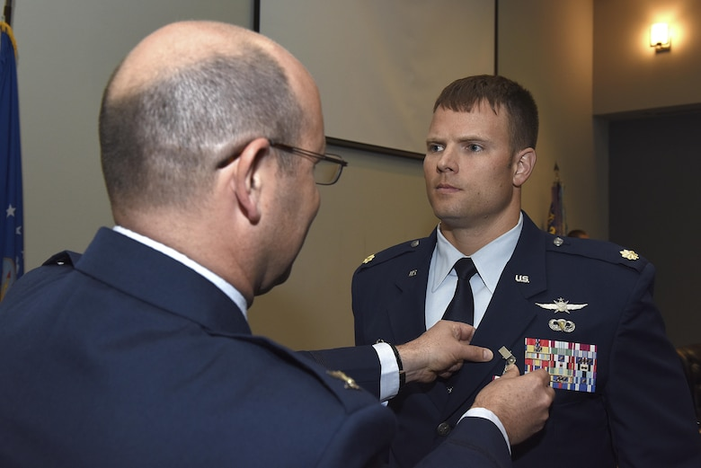U.S. Air Force Maj. Stephen Maddox, 17th Communications Squadron commander, stands at attention as Col. Christopher Harris, 17th Mission Support Group commander, pins on a Meritorious Service medal during the 17th CS change of command ceremony at the Event Center on Goodfellow Air Force Base, Texas, May 31, 2017. Maddox received the medal for outstanding service to his unit by providing new equipment and deployment opportunities for Airmen despite low manning