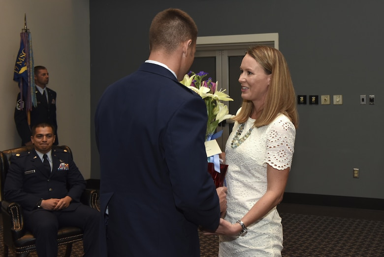 U.S. Air Force Maj. Stephen Maddox, 17th Communications Squadron commander, hands flowers to his wife during the 17th CS change of command ceremony at the Event Center on Goodfellow Air Force Base, Texas, May 31, 2017. During change of command ceremonies it's custom to give flowers to a departing commander's wife as a symbol of appreciation for their support.