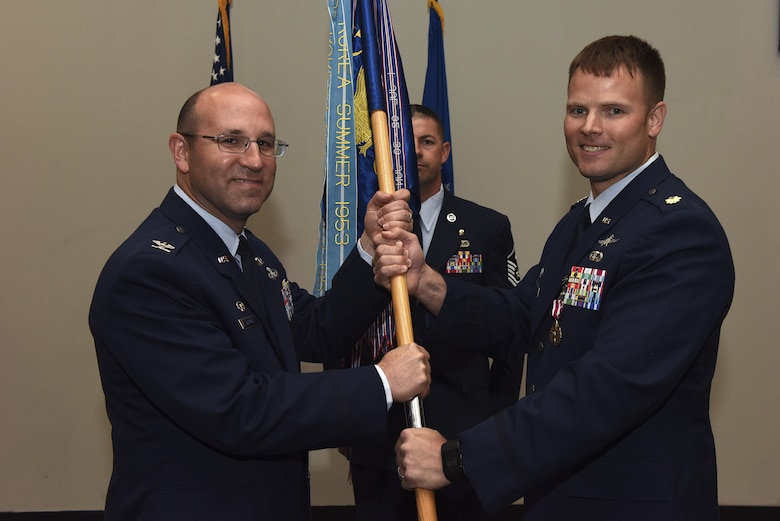 U.S. Air Force Col. Christopher Harris, 17th Mission Support Group commander, receives the unit guideon from Maj. Stephen Maddox, 17th Communications Squadron commander, during the 17th CS change of command ceremony at the Event Center on Goodfellow Air Force Base, Texas.