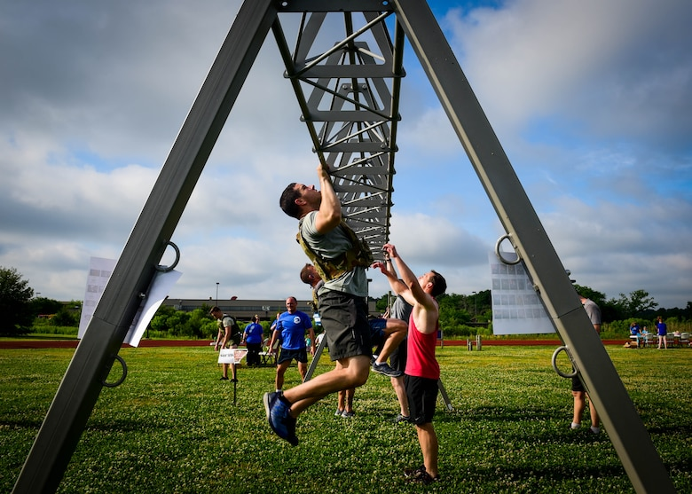 U.S. service members and their families complete the pull-up portion of a Memorial Day Murph and Pararescue Workout event at Joint Base Langley-Eustis, Va., May 29, 2017. During the Murph Workout, members ran a total of two miles, performed a total of 100 pullups, 200 pushups and 300 squats. (U.S. Air Force photo/Staff Sgt. Areca T. Bell)