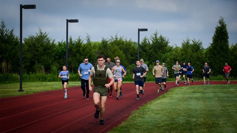 U.S. service members and their families participate in a 1-mile run during the Memorial Day Murph and Pararecue Workout event at Joint Base Langley-Eustis, Va., May 29, 2017. During the workout, members ran a total of two miles, performed a total of 100 pullups, 200 pushups and 300 squats. (U.S. Air Force photo/Staff Sgt. Areca T. Bell)