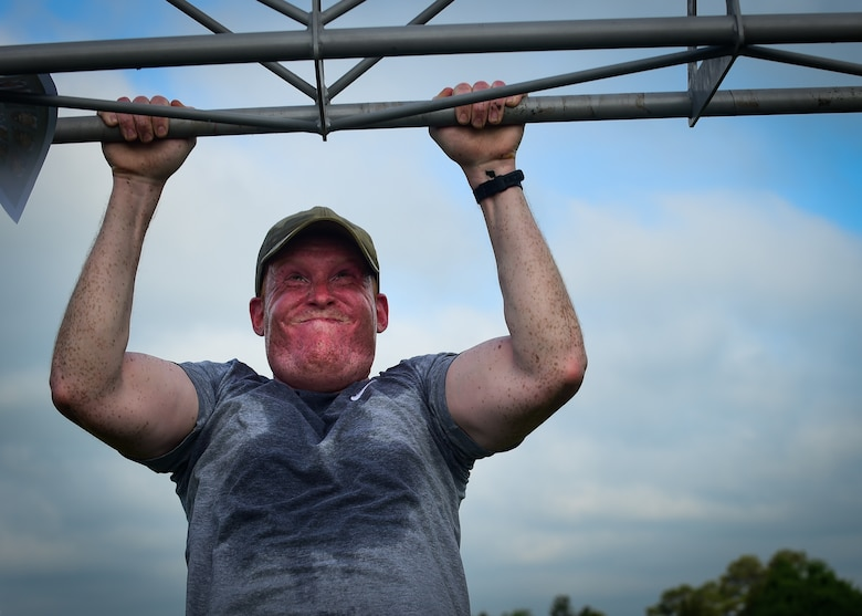 U.S. Air Force Staff Sgt. Holden, assigned to the 30th Intelligence Squadron, does a pull-up during a Memorial Day Murph and Pararescue Workout event at Joint Base Langley-Eustis, Va., May 29, 2017. Participants who participated in the Pararescue Workout ran a total of two miles, performed a total of 100 pullups, 400 burpees, 300 squats, 100 sit-ups and 400-meter tire flip. (U.S. Air Force photo/Staff Sgt. Areca T. Bell)(Last name withheld for security purposes)
