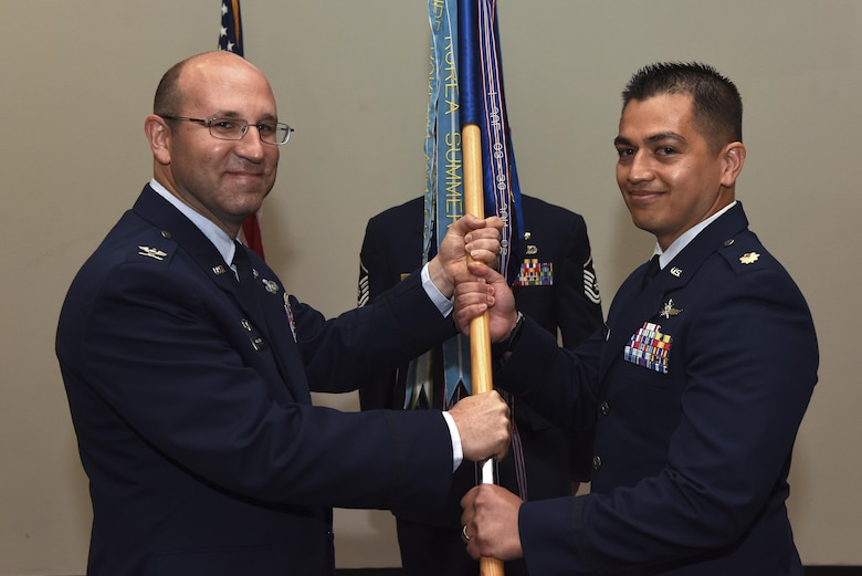 U.S. Air Force Col. Christopher Harris, 17th Mission Support Group commander, passes the unit guideon to Maj. Mark Walkusky, the new 17th Communications Squadron commander, during the 17th CS change of command ceremony at the Event Center on Goodfellow Air Force Base, Texas.