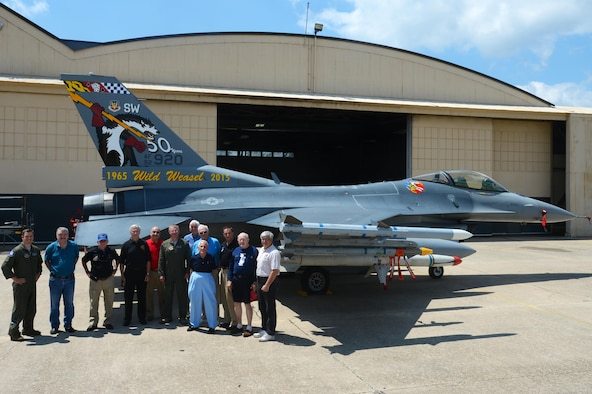 Retired U.S. Air Force Wild Weasels pose for a photo with present Wild Weasels in front of the 50th anniversary 20th Fighter Wing flagship F-16CM Fighting Falcon tail flash at Shaw Air Force Base, S.C., June 5, 2015. A conference is scheduled to be held June 22 to 25, 2017, in recognition of the Wild Weasels 52nd anniversary.