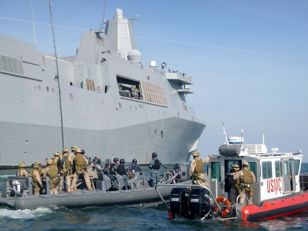 Marines from 2nd Reconnaissance Battalion conduct visit, board, search and seizure training alongside the USS San Antonio (LPD-17 off the coast of Virginia Beach, Va., while an Open Water Safety Craft floats nearby. The OWSC has been in service since 2006, and is used as an emergency vessel during waterborne training operations. Marine Corps Systems Command is working with Marine Corps Logistics Command and the National Marine Center to refurbish 28 boats in the Corps inventory. (U.S. Marine Corps photo by Jake Feeney)